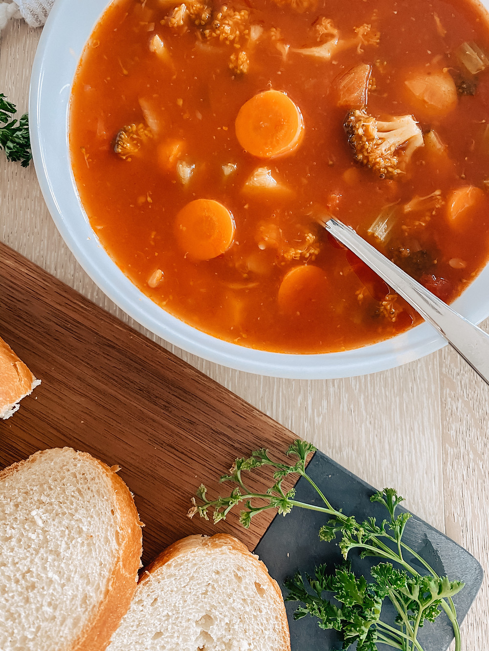 A bowl of hearty vegetable soup sits on the table surrounded fresh herbs and fresh sliced bread.