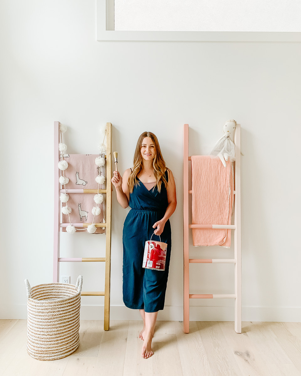 A girl standing beside some colourful wooden blanket ladders holding a paint can and a paint brush.