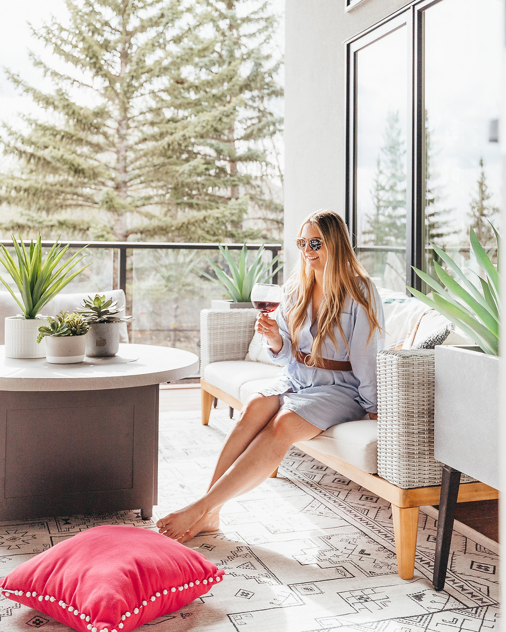 A girl sitting on a modern outdoor patio sofa holding a glass of red wine next to a fire table and a pink outdoor cushion on a white and black area rug in the summer.