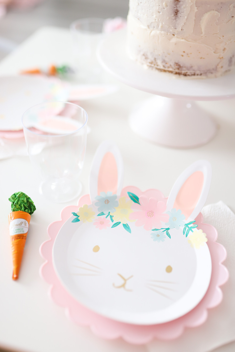 Pretty paper bunny rabbit plates on a white table set for a bunny Easter party.