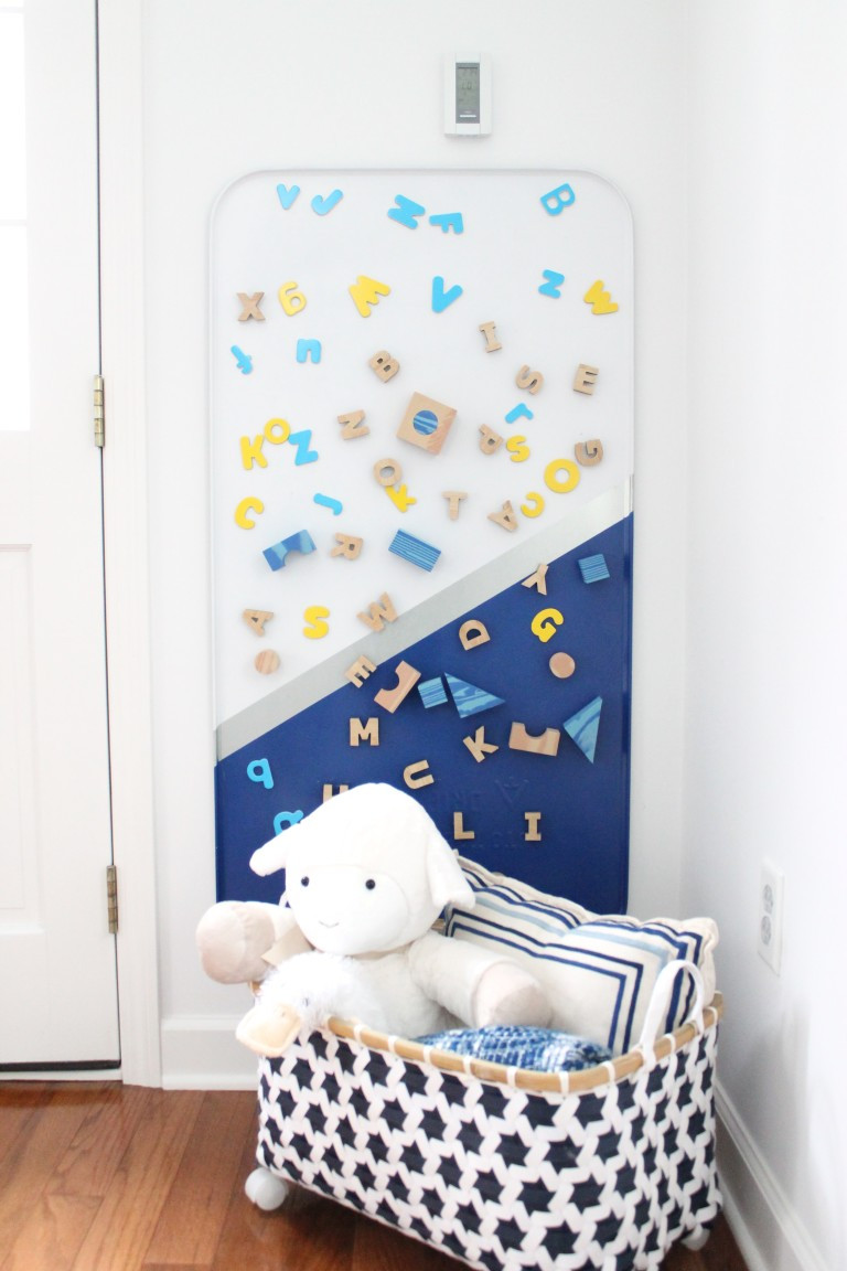 An easy childrens magnet board in playroom with storage basket and toy lamb