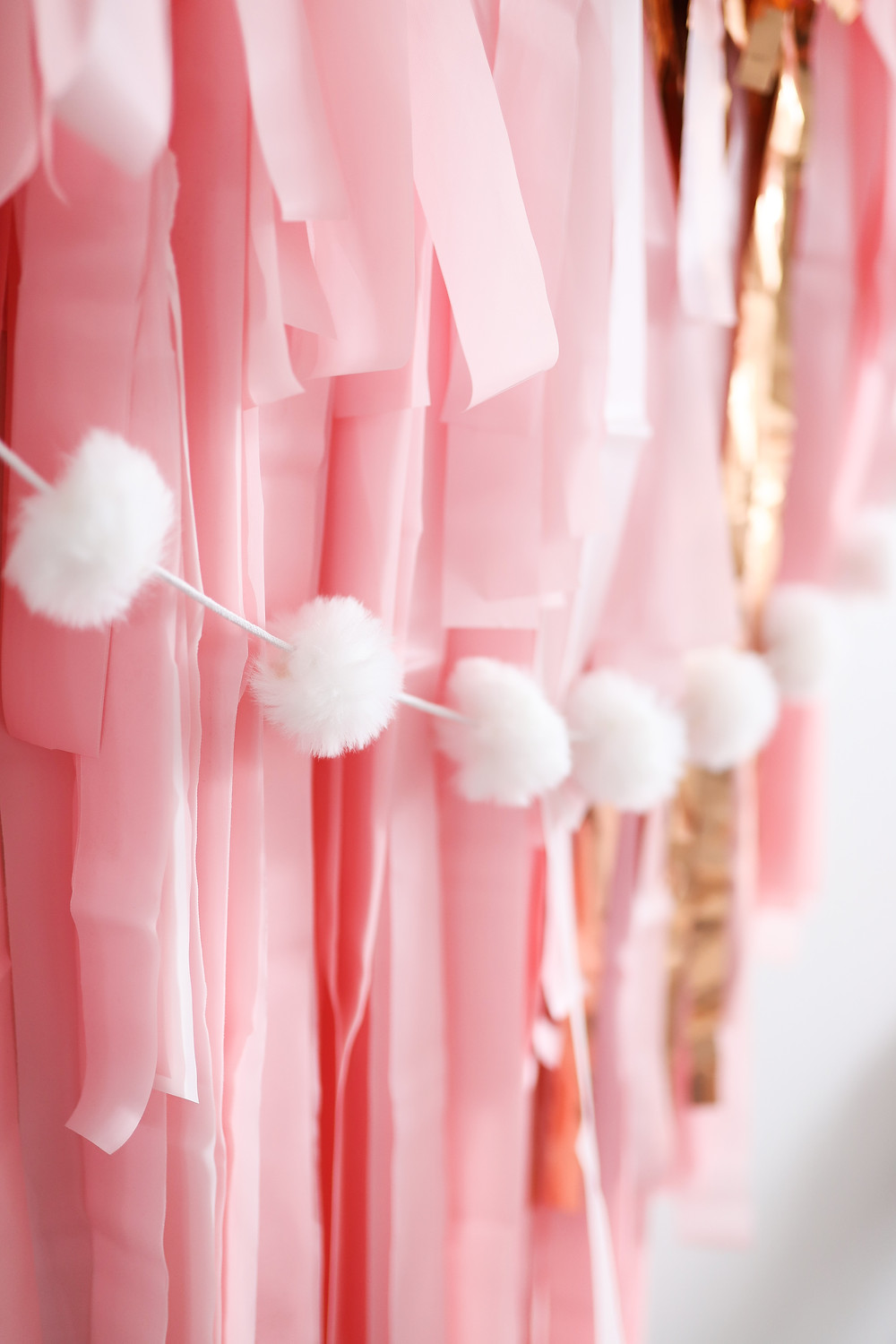 A pink and gold paper party banner with white pom poms hanging on the wall for a birthday celebration.
