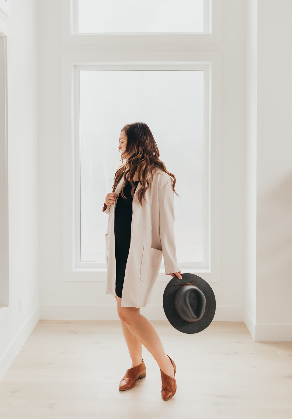 A girl is standing wearing an oversized nude coat holding a hat.