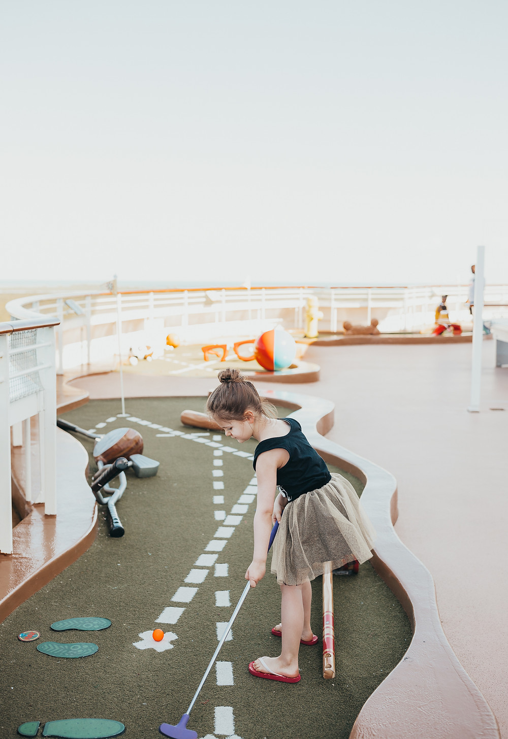 A little girl playing mini golf outside on a Disney Cruise ship.