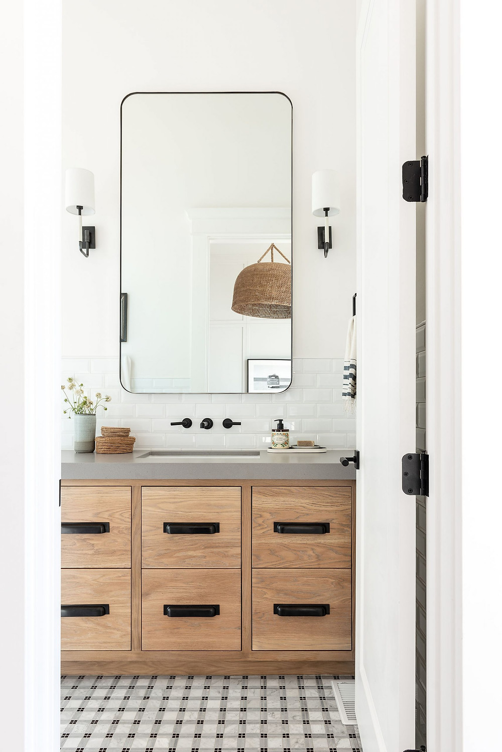 wood bathroom vanity with 6 drawers black handles two sconces flanking large black framed mirror white subway backsplash concrete grey countertop and marble mosaic floor tile