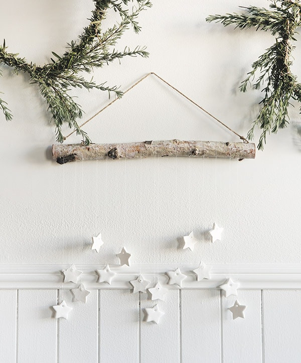 A Scandinavian style wall hanging made from natural tree branches, wood and white star shapes hags on the wall for Christmas.