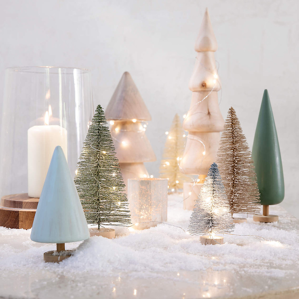 A modern and minimal Christmas display with bottle brush trees and wooden tree ornaments sits amongst white candles and thinking fairy lights for a Christmas holiday display.