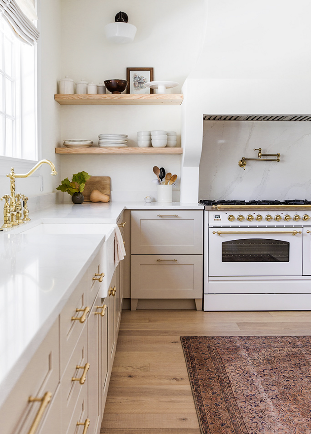 A bright high end kitchen with a gas range and gold faucets and some natural wood open shelves.