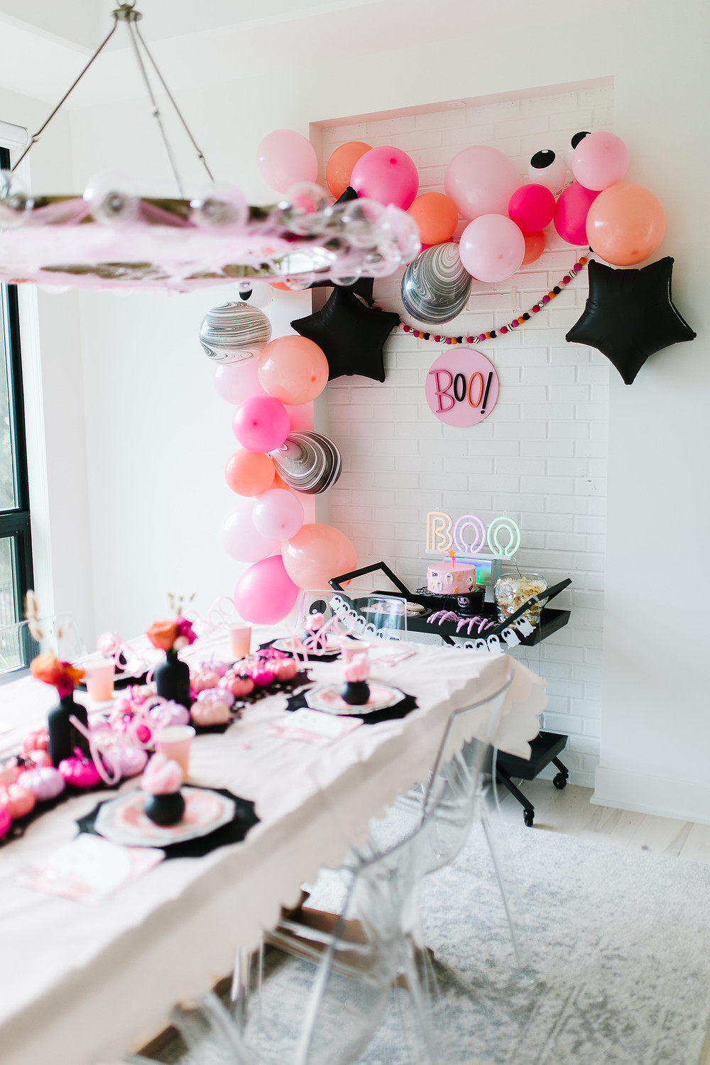 A ghoul gang halloween party with ombre pink and orange decorations, balloons, spider webs and glitter.