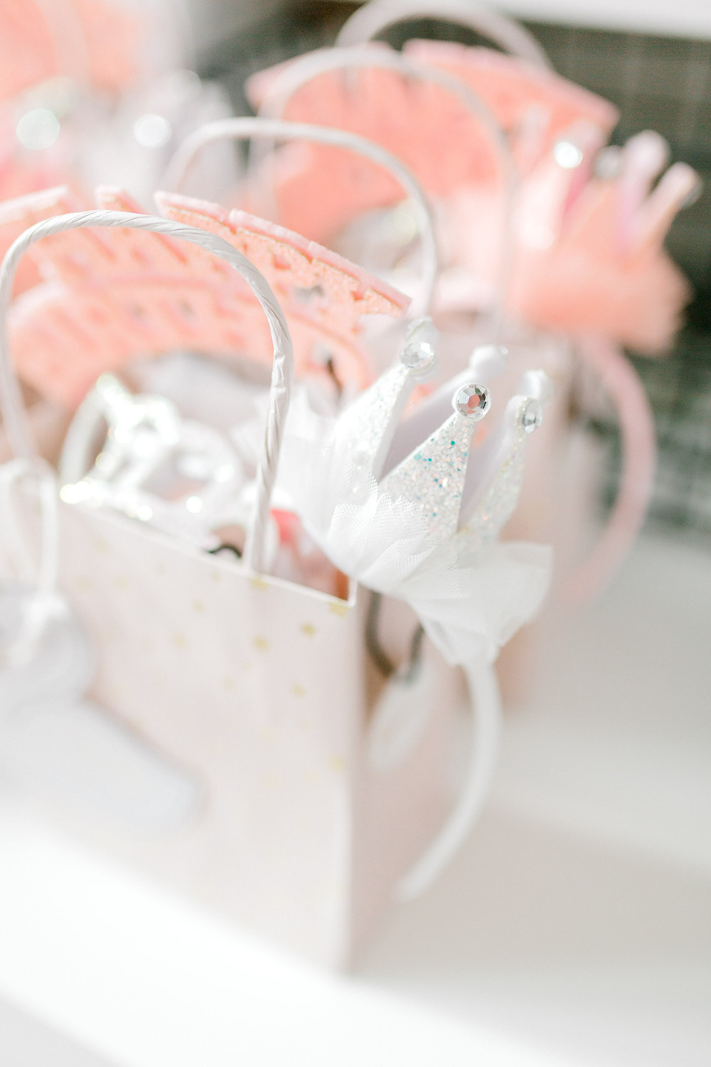 A white gift bag with gold stars, pink tulle, white crystal crown and a white swan attached to it at a nutcracker party.