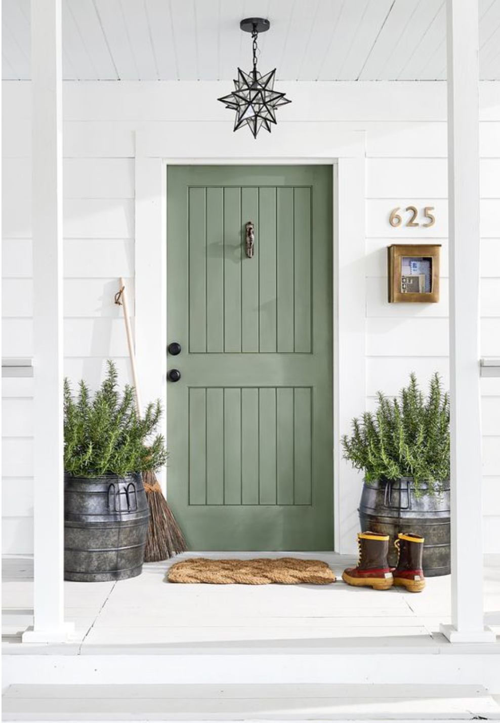 The front entrance door of a white home painted green with some black hardware.