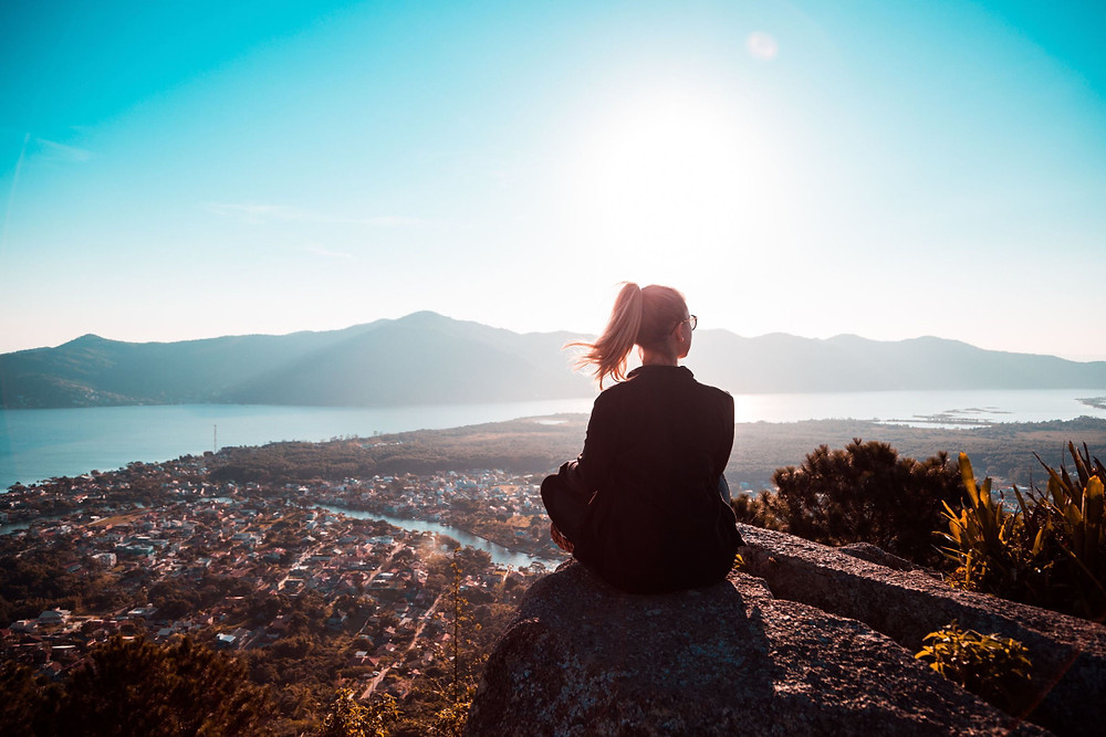 A girl sitting on top of a hill over looking the city.