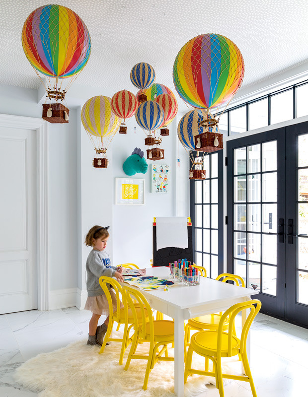 A childrens craft space with white table and yellow chairs and hot air balloons hanging above.
