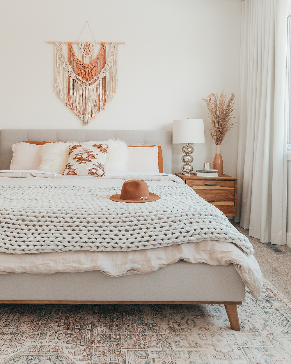 Cream and blush macramé wall hanging over grey headboard white and rust sheets with chunky grey throw on end of bed hat on end of bed area rug with wood side table and silver lamp with pampas grass in pink vase