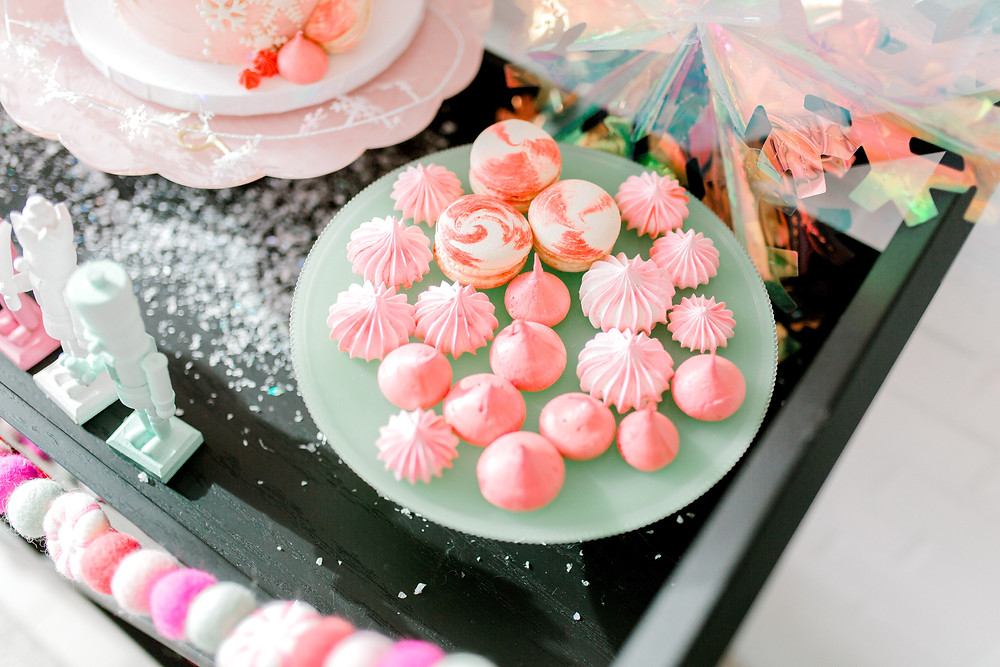 A dessert tray with pink meringue and pink and white macarons on a cart with pink and white garland and nutcrackers for a birthday party.