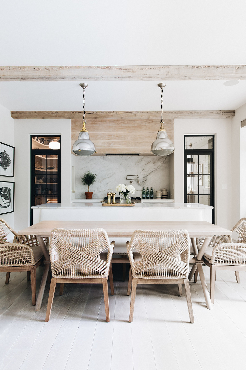 brushed aluminum and brass pendant lights over kitchen island with exposed beams wood hood fan detail marble backsplash dark wood pantry doors woven wood chairs at dining table light hardwood floors