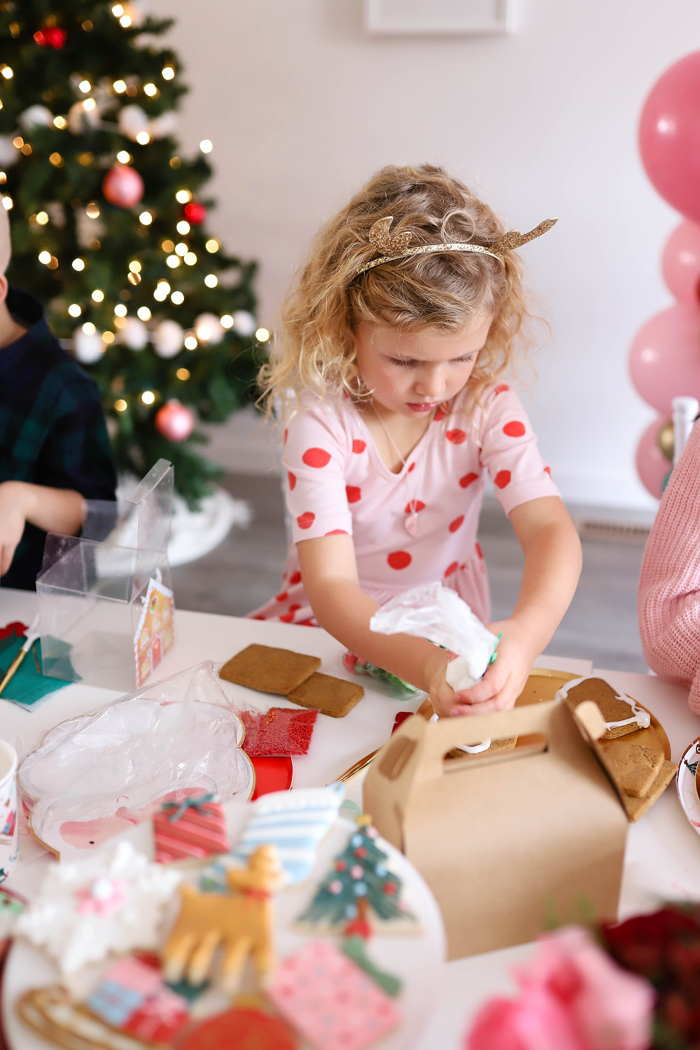 A little girl decorating a gingerbread house at a holiday Christmas party in front of a christmas tree.