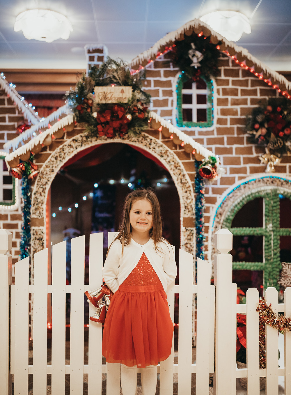 A little girl in a red dress standing in front of a giant gingerbread house.