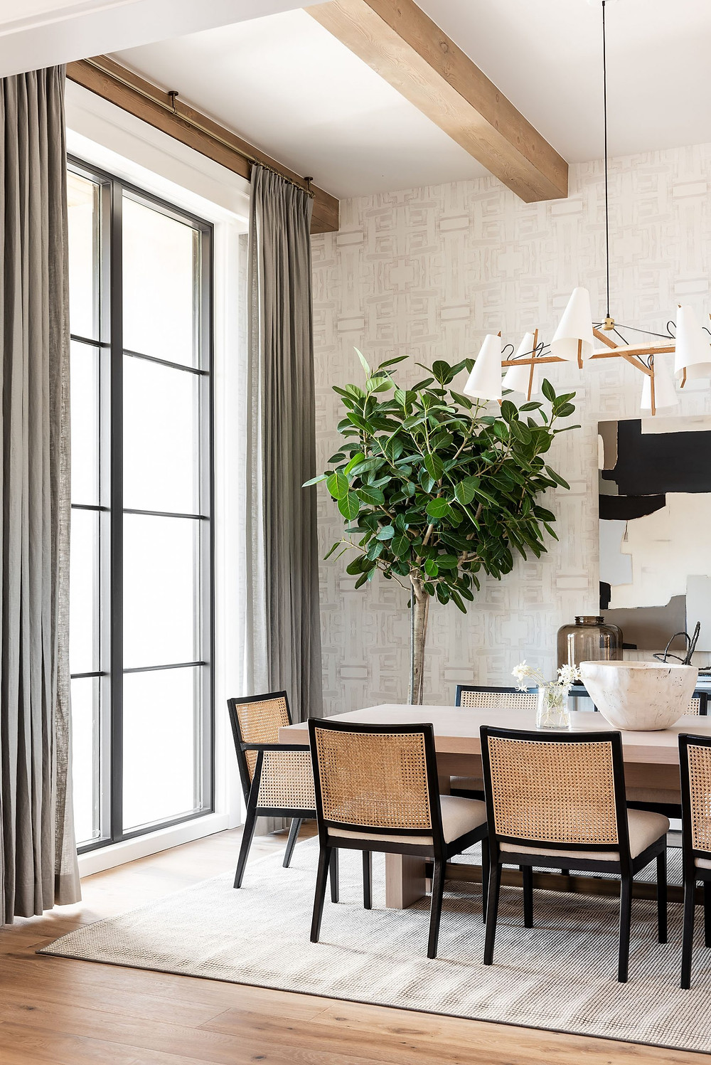 wood beam accented ceiling wallpaper soft grey drapery black framed windows dining table with black framed chair on beige area rug hardwood floors floor plant
