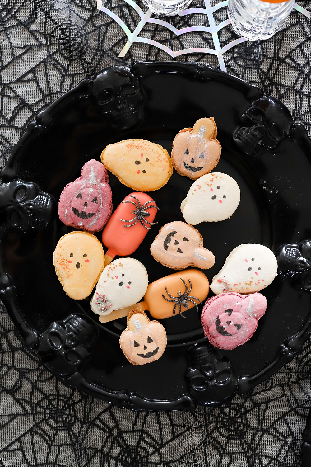 A black and metallic spider web cloth with a black skeleton serving tray holding an assortment of white, orange, yellow, and pink pumpkin, spider, and ghost kid's halloween cookies.