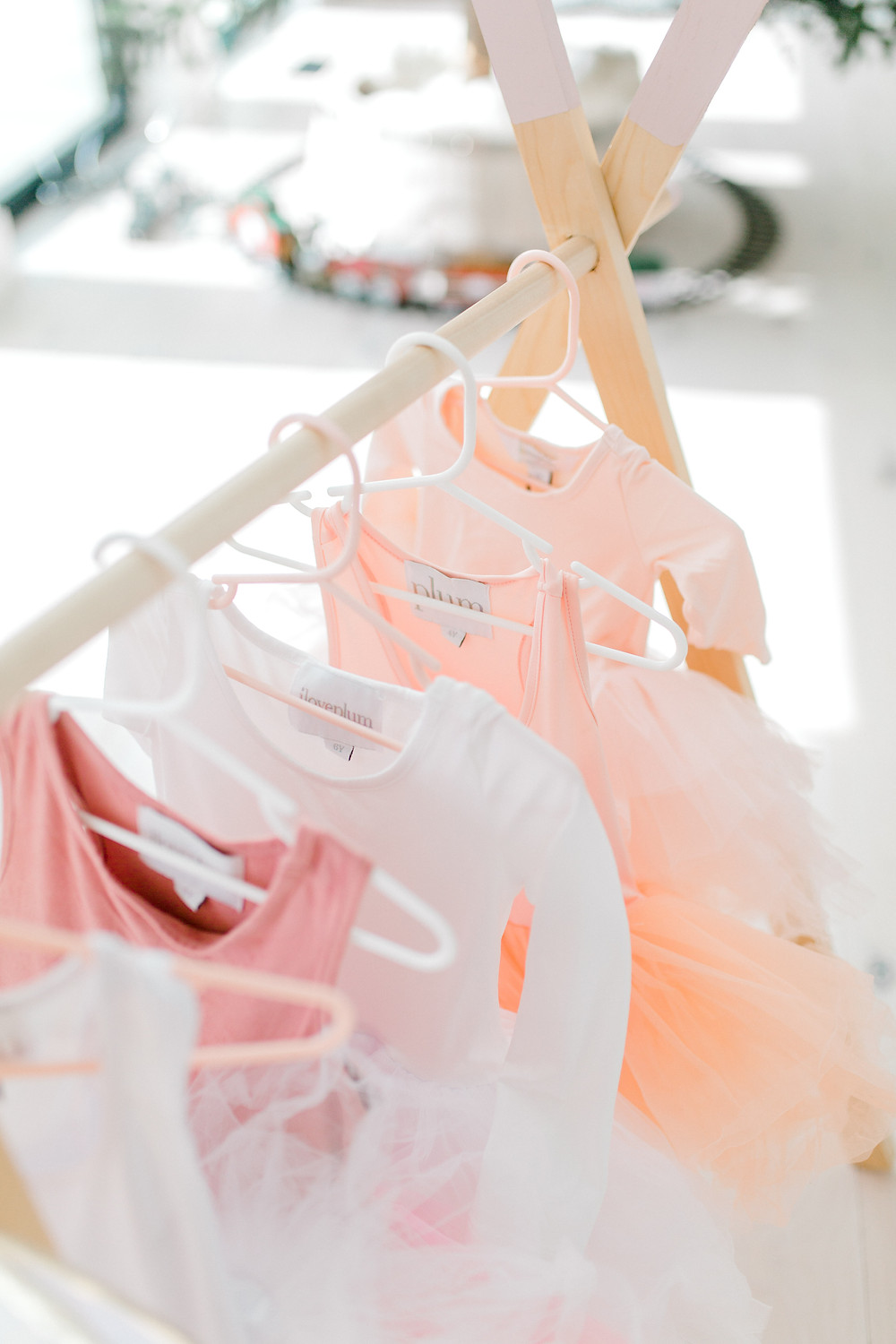 a clothing rack stands in a room with pink, peach and white tutu's