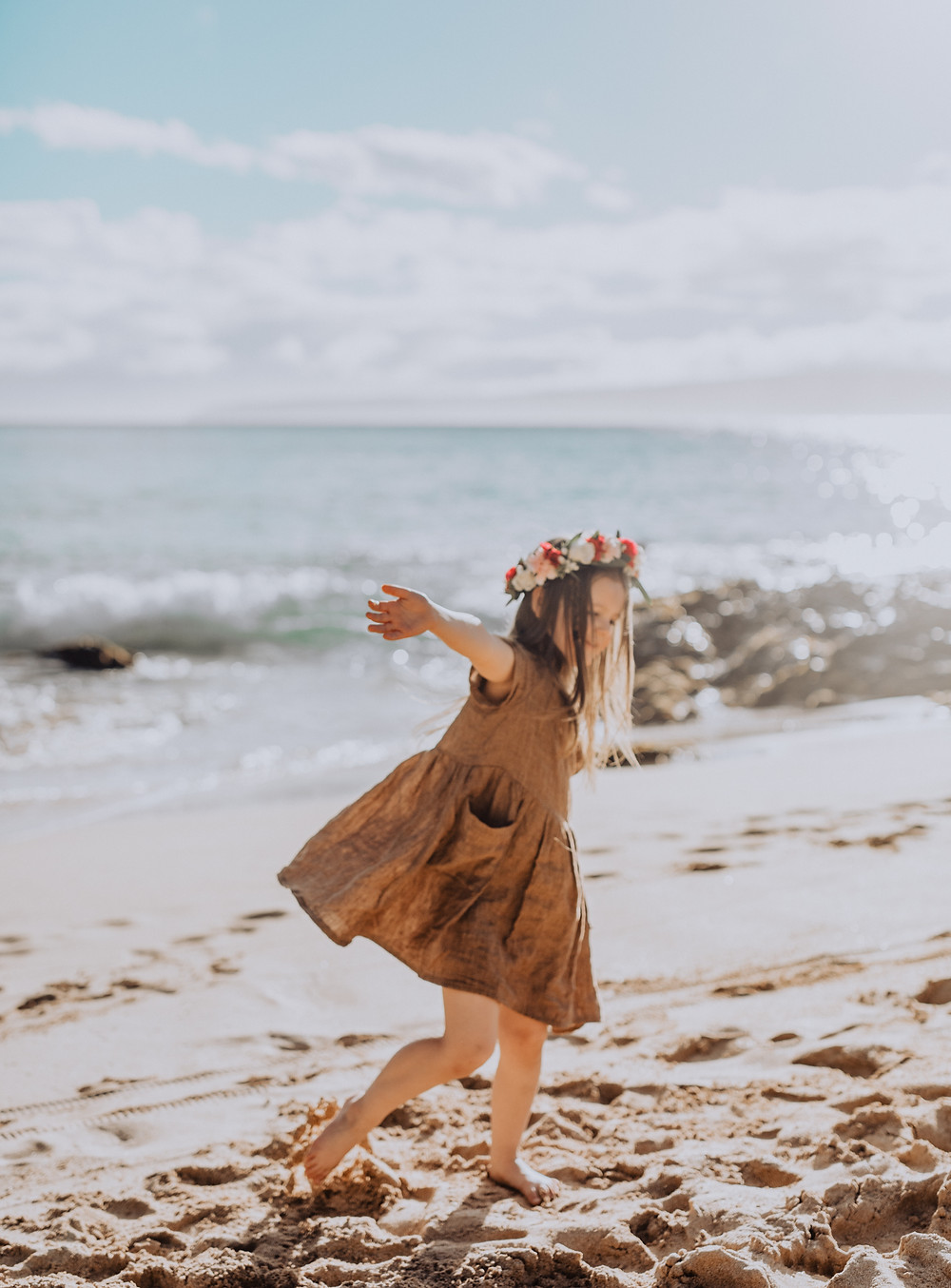 A little girl is playing on the beach in hawaii in a linen dress.