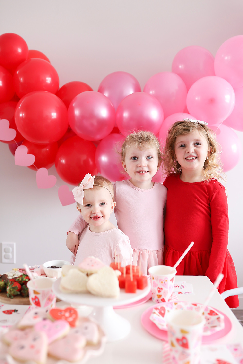 Three little girls smiling at the camera at a Valentine's Day party.