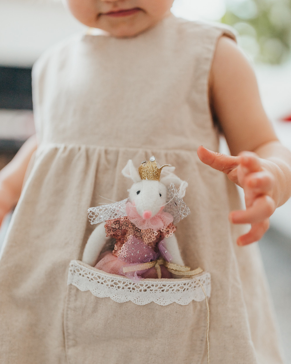 A baby girl at christmas time playing with a glitter mouse Christmas decoration in her pocket.