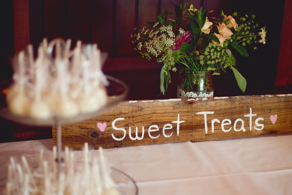 A table of cake pops and a wooden sign at a wedding.