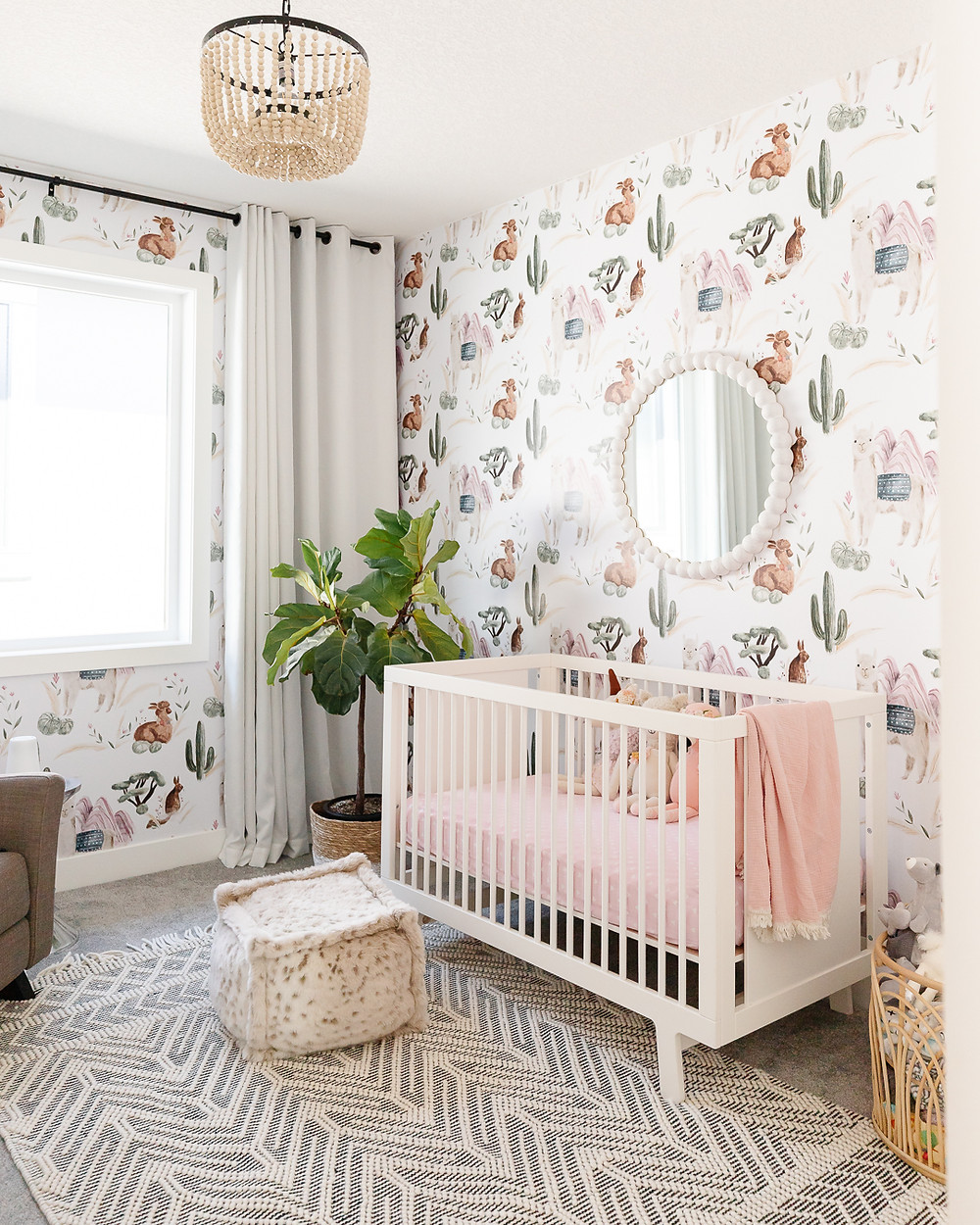 Nursery with wood bead chandielier white crib with white mirror llama accent wallpaper fiddle leaf fig in basket on floor patterned area rug woven basket with stuffed animals faux fur pouf and armchair