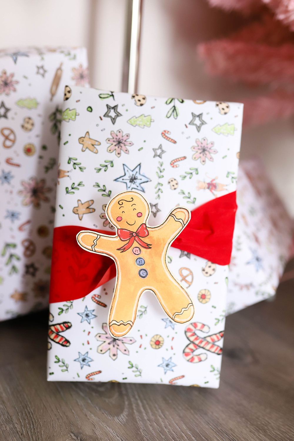 A Christmas present wrapped with gingerbread men and festive modern wrapping paper.
