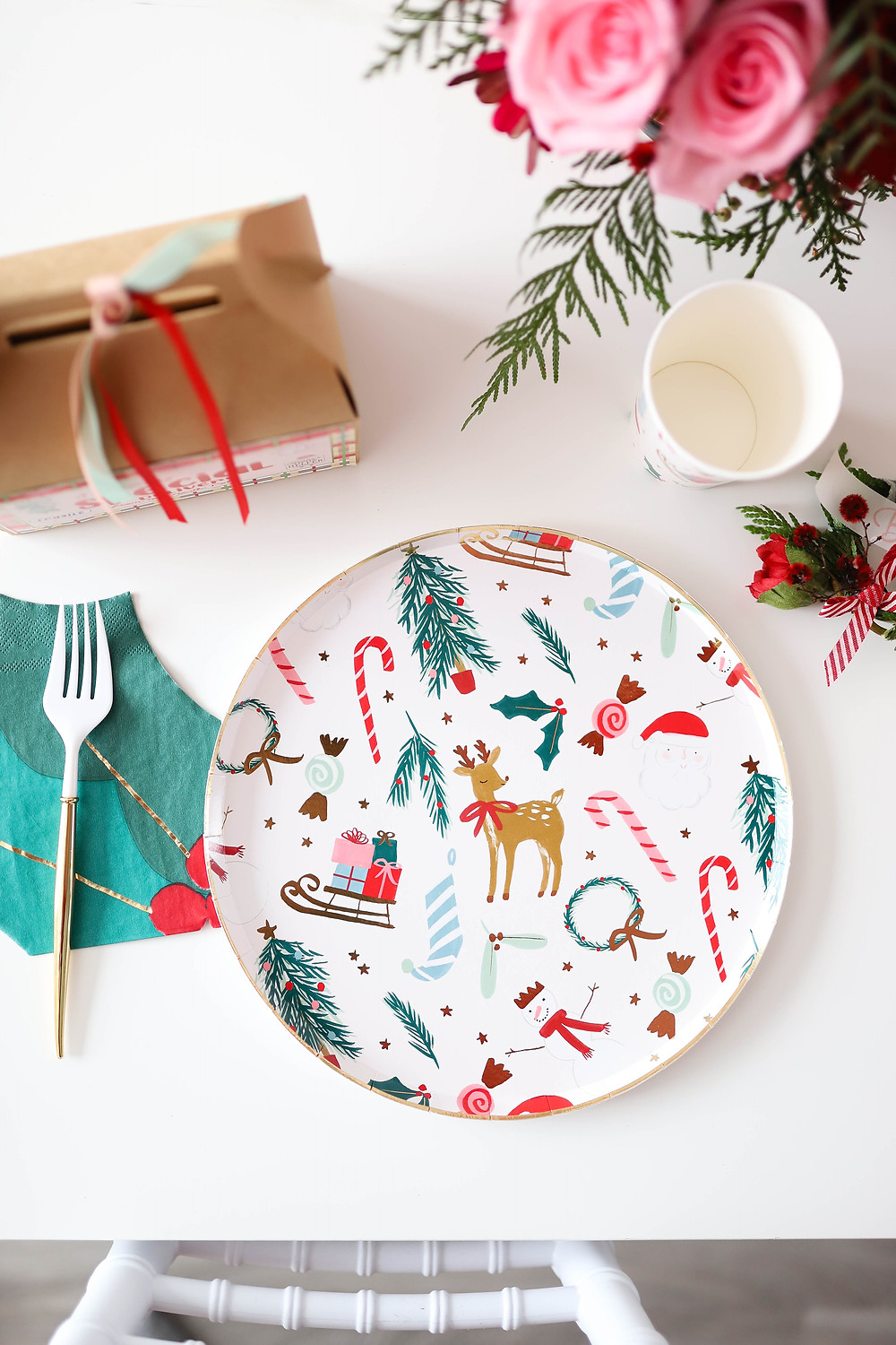 A christmas paper plate on a white table sitting next to holiday flowers, mistletoe napkins and a gift box.