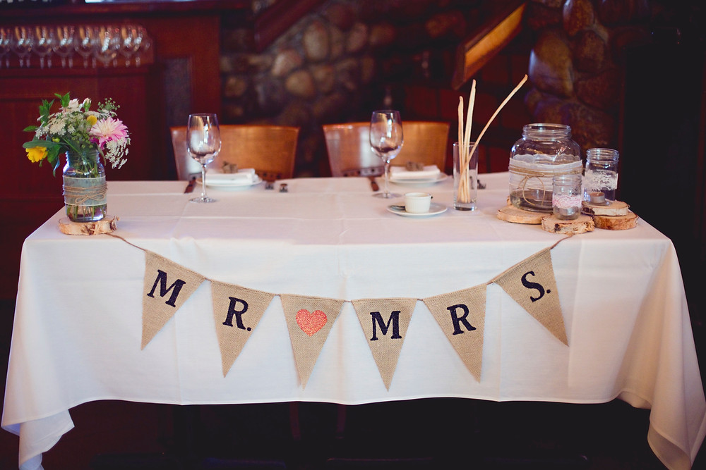 A bride and grooms sweetheart table is topped with a white linen table cloth and show off a beautiful garden bouquet in a lace wrapped mason jar on top of wooden rounds finished off with a mr. and mrs. burlap banner in a rustic Italian restaurant.
