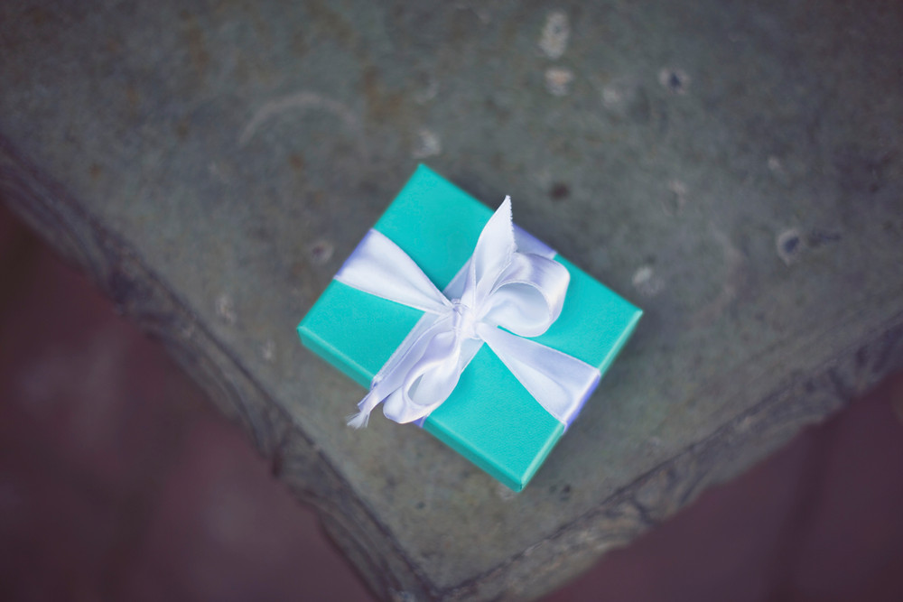 A Tiffany box sitting on a concrete bench with the bride and groom on their wedding day.