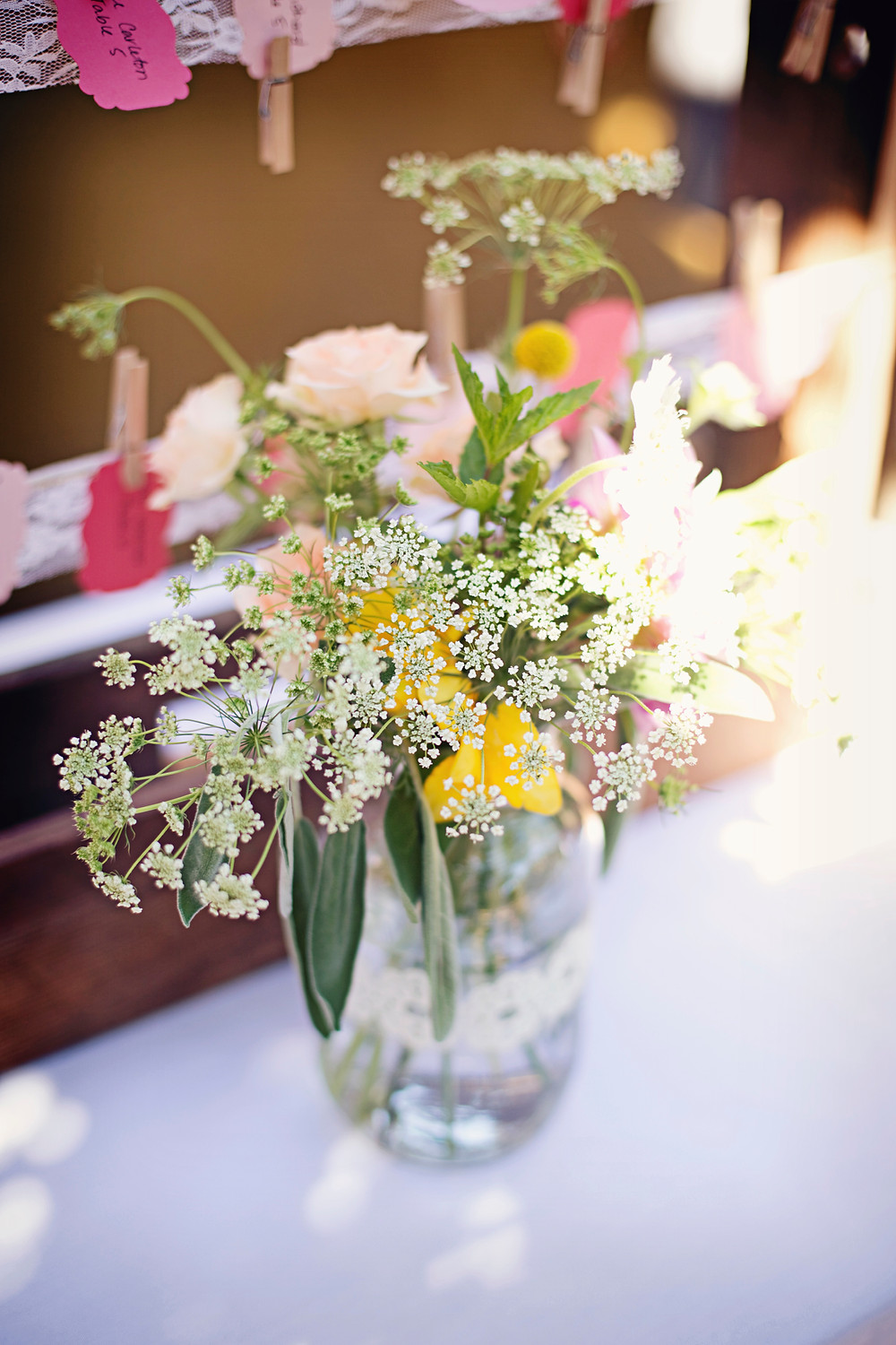 A vase of garden flowers sitting in a clear vase at a rustic Italian inspired wedding.