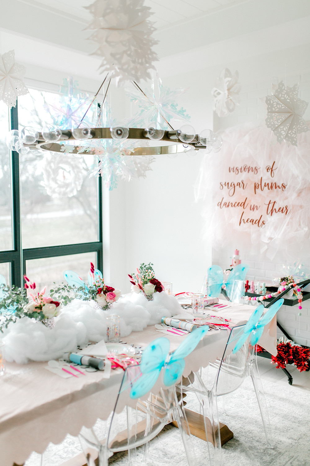 Sugar plum nutcracker birthday party with hanging paper and clear snowflakes and blue butterfly wings with floral centrepieces.