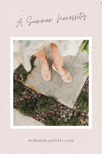 A girl standing outside in a garden looking down at her sandals.