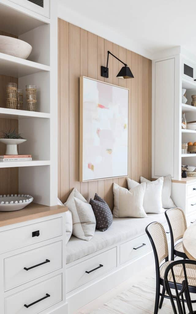 wood shiplap details white cabinets black handles black and gold wall sconce artwork bench upholstered seating with throw pillows wood chairs with woven seats dishes cups open shelving storage