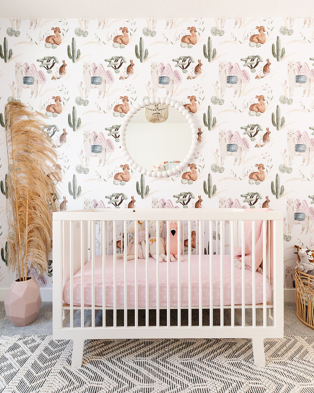 Nursery with white crib and fitted pink sheet white mirror on wall with llama wallpaper detail pampas grass in pink vase on floor wood bead chandelier