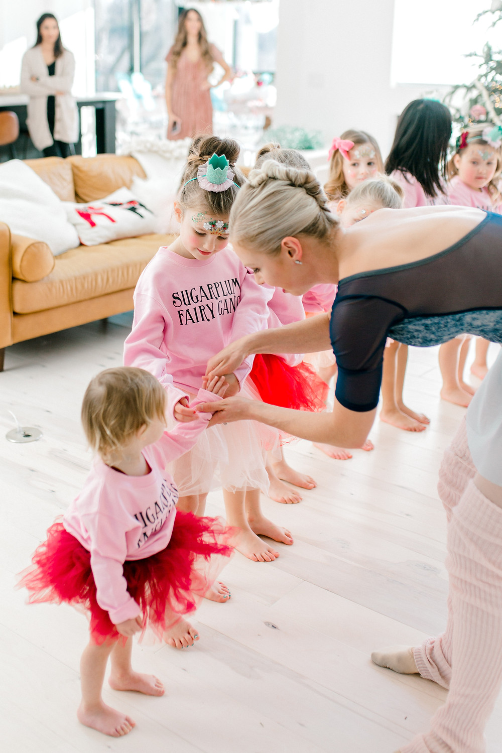 A group of girls at a birthday party are dressed in red, white and pink tutus dancing as ballerinas in a living room.