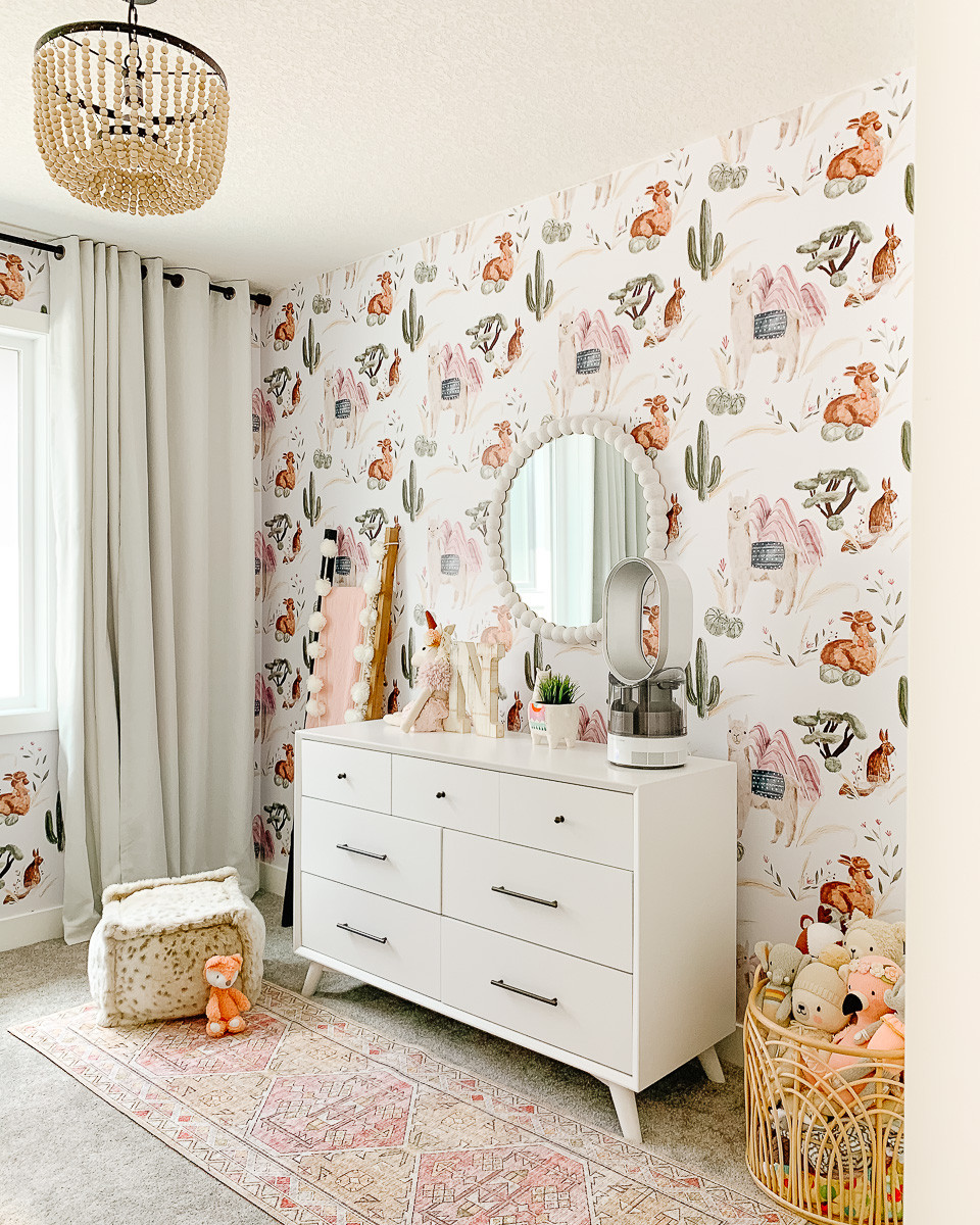 A boho nursery with a white dresser, a wooden ball chandelier, a round mirror and some white curtains with llama wallpaper.