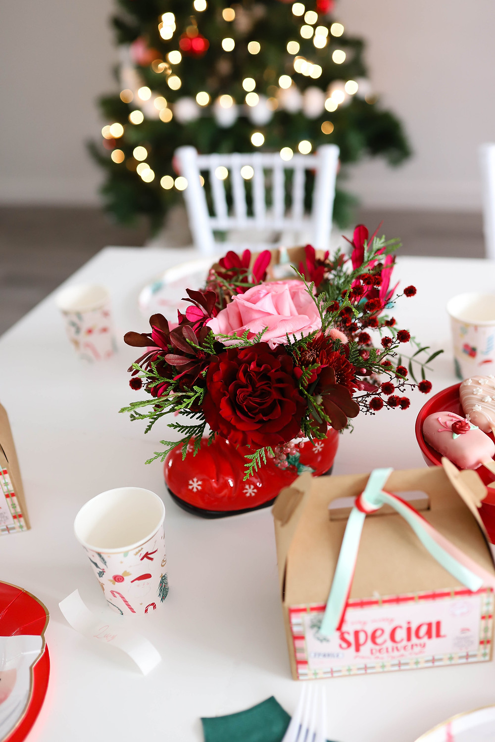 A red pink and green holiday floral bouquet set on a white table for christmas.