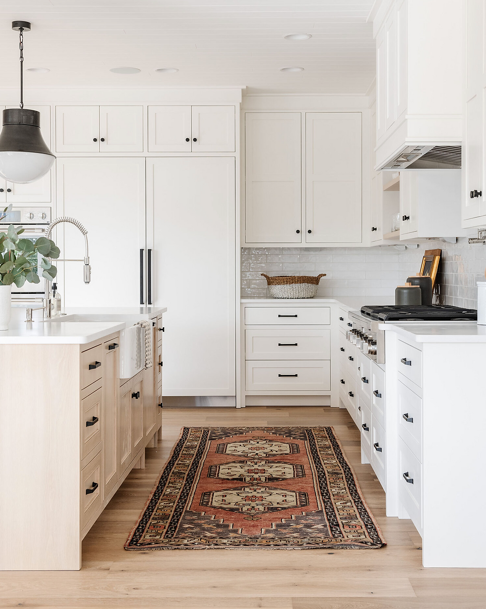 A white kitchen with black hardware and a moroccan style rug.