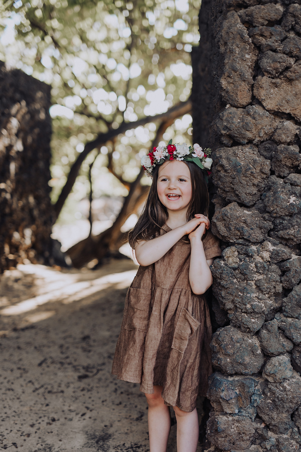 A little girl stands against a rock wall smiling happily.