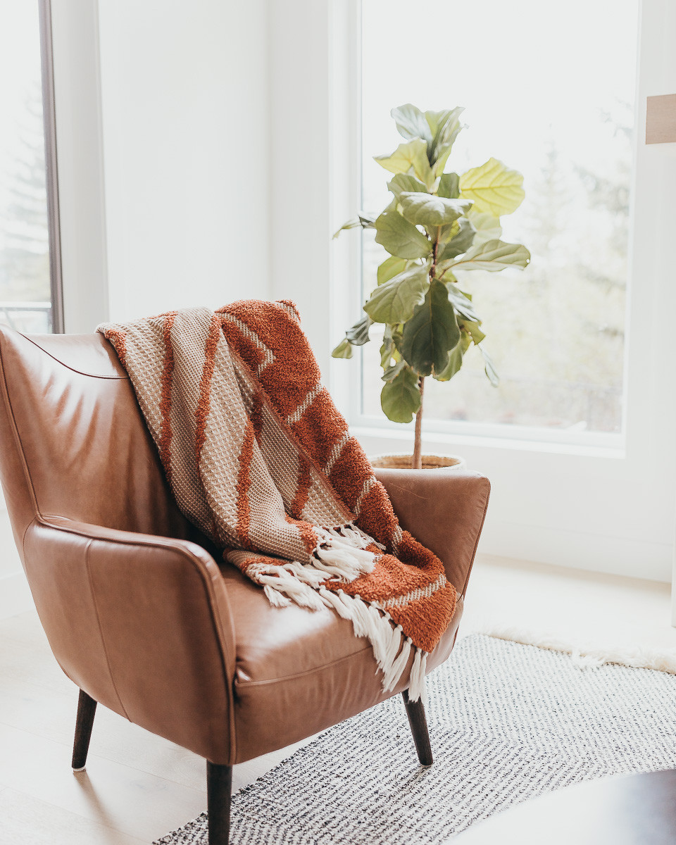 A fringe throw blanket laying across a brown leather chair.