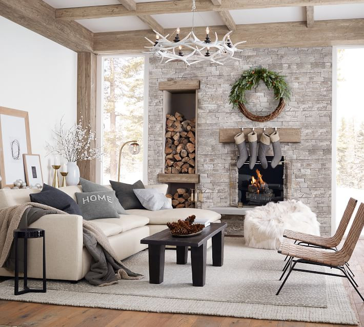 A modern and minimal living room set up with Scandinavian decor displays stockings hanging above the stone fireplace and an antler chandelier above a white section sofa at Christmas time.