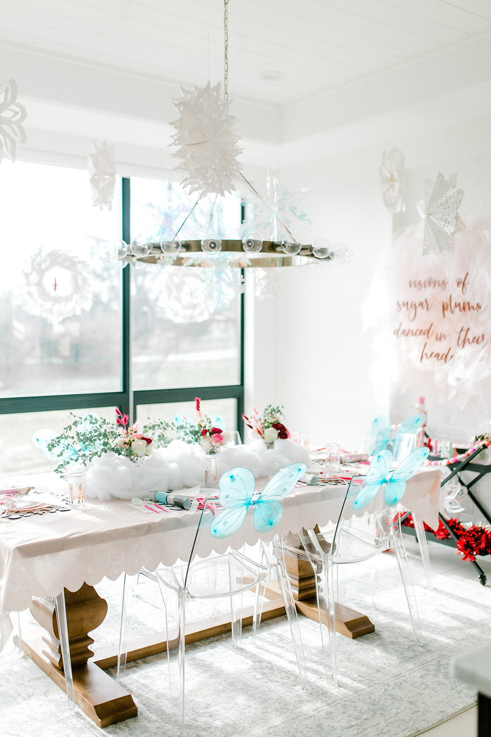 A sugar plum nutcracker birthday party with hanging paper and clear snowflakes and blue butterfly wings with floral centrepieces.