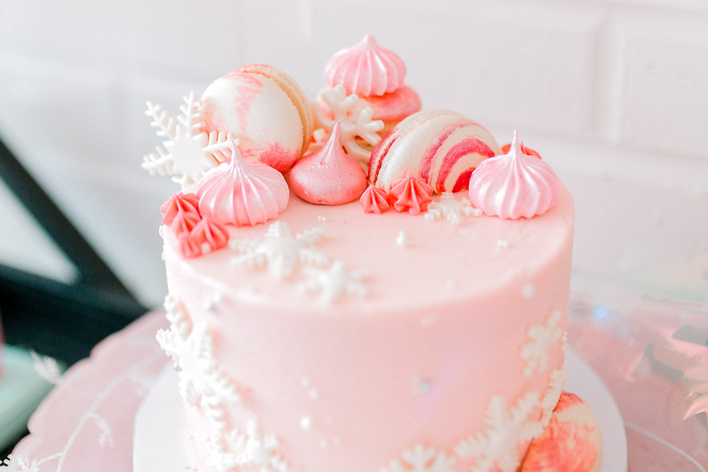 A pink birthday cake with white snowflakes, white macarons, pink icing with beads on a white platter at a nutcracker birthday party.