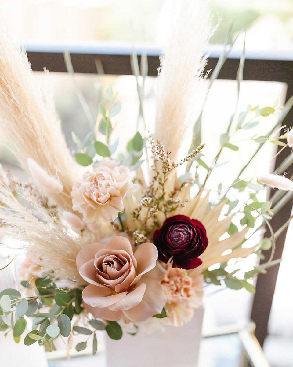 A beautiful bouquet of flowers with dried palm leaves and pampas grasses placed in a white vase.