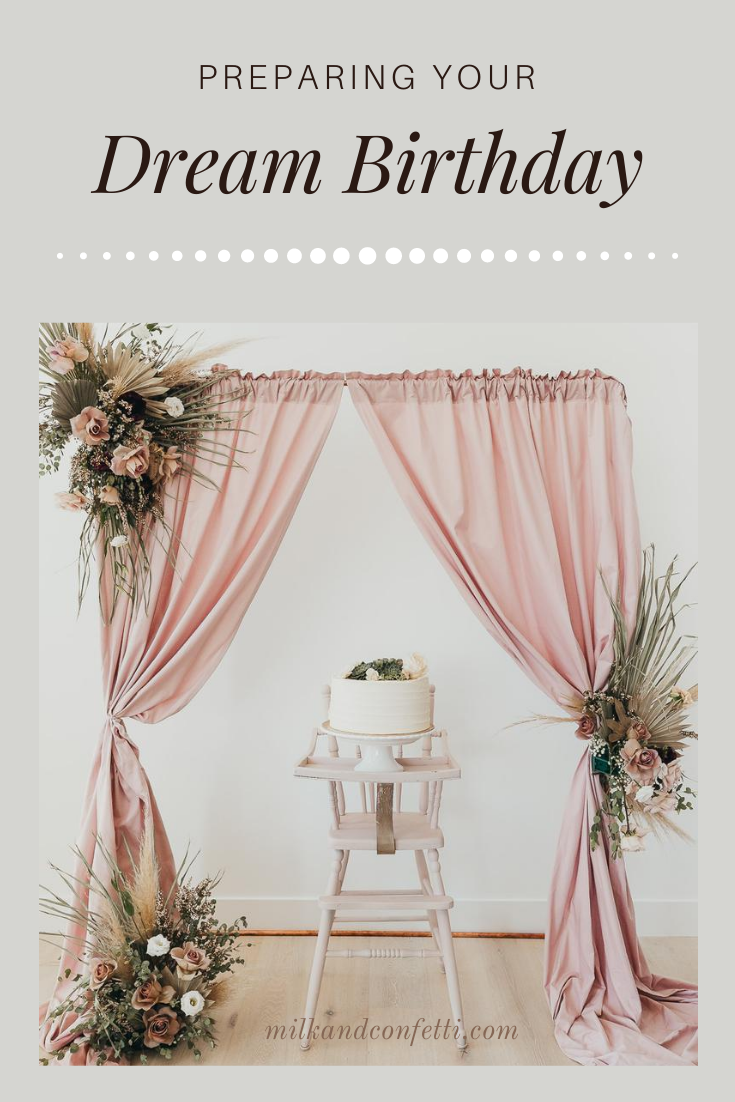 A white cake on a white cake sand sitting on a blush high chair in front of some boho floral arrangements.